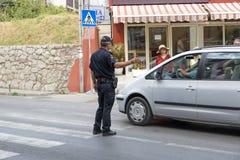 De politieagent leidt verkeer op de voetgangersoversteekplaats Budva, Montenegro stock afbeeldingen