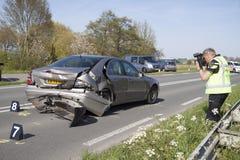 De politieagent neemt beelden, beelden van een beschadigde auto Royalty-vrije Stock Afbeelding