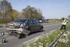 De politieagent neemt beelden, beelden van een beschadigde auto voor de verzekering Stock Foto's