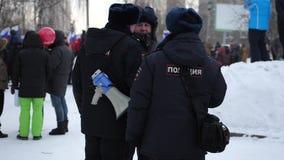 De politieagenten met een mondstuk bewaken Strike tegen valse verkiezingen van de Voorzitter van de Russische Federatie, Novosibi stock videobeelden