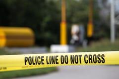 De politielijn doet geen kruis met benzinestationachtergrond in misdaadsce stock afbeeldingen