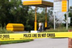 De politielijn doet geen kruis met benzinestationachtergrond in misdaadsce stock foto
