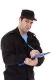 De politieman schrijft een kaartje Stock Afbeeldingen
