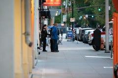 De politiemannen gaan met een Latino mens op de straat interactie aan stock foto