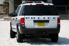 De politiewagen van het strand die op zandig strand wordt geparkeerd Stock Afbeeldingen