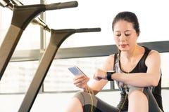 De polsslag van de het gebruiks smartwatch controle van de sport Aziatische vrouw het luisteren musi Stock Afbeeldingen