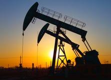 De pomp van de olie tegen het plaatsen van zon Stock Foto's
