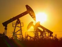 De pomp van de olie tegen het plaatsen van zon Royalty-vrije Stock Afbeelding