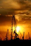 De pompen van de olie bij zonsondergang Royalty-vrije Stock Foto