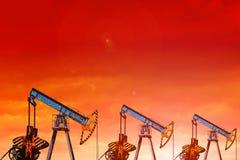 De pompen van de olie bij zonsondergang Oranje Hemel Royalty-vrije Stock Afbeelding