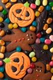De pompoen, de knuppel en de peperkoek mens-vampier van Halloween boven geschotene koekjes en kleurrijk suikergoed stock foto's