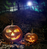 De pompoenen van Halloween op rotsen bij nacht Stock Foto's