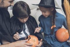 De Pompoenen van vaderhelps children prepare voor Halloween royalty-vrije stock fotografie