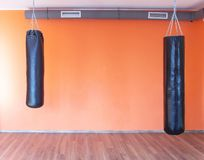 De ponsenzakken voor sporten en vechtsporten hangen in de gymnastiek tegen de achtergrond van de oranje muur, exemplaarruimte royalty-vrije stock afbeelding