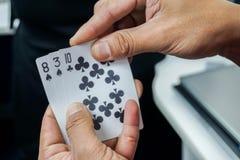 De pookkaart van het mensenspel in handen voor het gokken Stock Fotografie