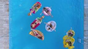 De pool ontspant, bedrijf van aantrekkelijke meisjes in badpak die op Opblaasbare ringen en matras bij poolside binnen drijven stock videobeelden