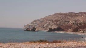 De pool van Aphrodite, de rotsachtige blauwe hemel van strand hoge klippen en overzees, Overzeese kust met rotsen, niemand stock videobeelden