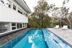De pool van de oneindigheidsrand in binnenplaats van midden van de eeuw Australisch huis royalty-vrije stock foto's