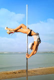 De pooldans van de vrouwenoefening tegen overzees landschap. Royalty-vrije Stock Foto