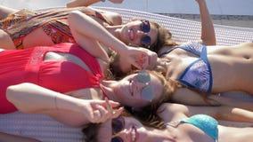 De poolpartij, blije meisjes met mooie cijfers in zwempakken die overhandigt hallo het liggen op deckchair dichtbij Poolside-clos