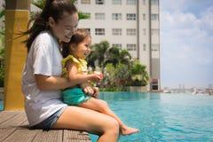 De pooltijd van de pretfamilie met moeder en kind De tijd van de vakantie stock foto's