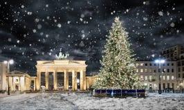 De Poort van Brandenburg in Berlijn, met Kerstboom en sneeuw Stock Afbeeldingen