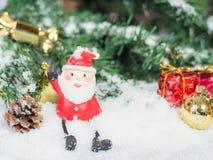 De pop en glod Kerstmisballen van de Kerstman en rode doos in sno Stock Afbeelding