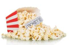 De popcorn morste van een vierkante doos en een grijs die filmkaartje op wit wordt geïsoleerd Stock Foto's