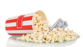 De popcorn was verspreide uit doos en filmkaartjes, op wit stock foto