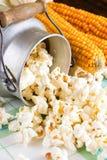 De popcorn wordt gemorst van kan naast maïskolven die Stock Fotografie