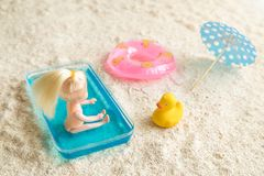 De poppenzitting van het babymeisje in jonge geitjes zwembad naast opblaasbare poolvlotter, cocktailparasol en rubbereend op het  stock fotografie