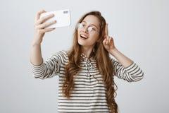 De populaire manier blogger maakt nieuwe vlog gebruikend smartphone Portret van positief zeker Europees meisje die v-teken tonen stock afbeeldingen