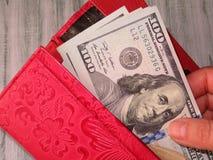 De portefeuille met Amerikaanse dollars in de vrouwelijke handen, betaalt concept royalty-vrije stock afbeelding