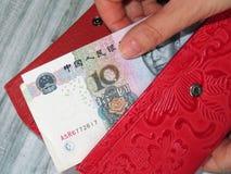 De portefeuille met yuansnota's in de vrouwelijke handen, betaalt concept stock afbeelding