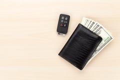 De portefeuille van het geldcontante geld en auto verre sleutel op houten lijst Stock Fotografie