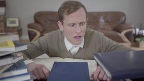 Is de portret jonge bescheiden geklede mens die uit van achter het bureau in het bureau gluren, vele boeken op de lijst E stock video