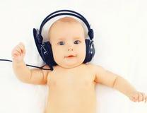 De portretbaby luistert aan muziek die in hoofdtelefoons op het bed liggen stock foto