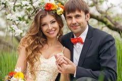 De portretjonggehuwden in de weelderige lente tuinieren Stock Fotografie