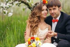 De portretjonggehuwden in de weelderige lente tuinieren Stock Foto
