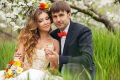 De portretjonggehuwden in de weelderige lente tuinieren Royalty-vrije Stock Fotografie