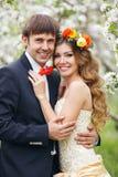 De portretjonggehuwden in de weelderige lente tuinieren Stock Afbeeldingen