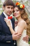 De portretjonggehuwden in de weelderige lente tuinieren Royalty-vrije Stock Afbeelding