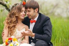 De portretjonggehuwden in de weelderige lente tuinieren Stock Afbeelding