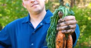 De portretkerel de landbouwer in een strohoed, robeoverhemd heft vuil op stock videobeelden