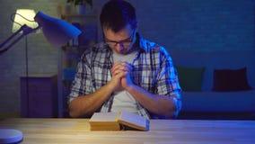 De portretmens zit bij een lijst en leest een gebed stock footage