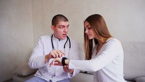 De portretten van arts verklaart patiënt hoe te om slim Horloge te gebruiken om hun gezondheid te controleren en op laag in het z stock video