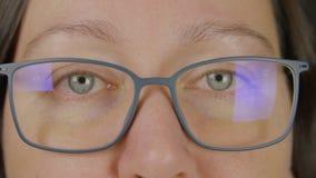 De portretvrouw die oogglazen dragen de blauwe ogen sluiten en openen, knipoogt, macro dicht omhoog geschotene studio stock footage