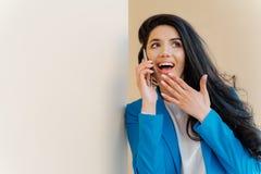 De positieve bedrijfsdame de open mond van rente, aanrakingenkin, opzij eruit ziet, gefascineerd door geruchten, heeft telefoonge stock foto