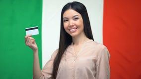 De positieve creditcard van de vrouwenholding tegen Italiaanse vlag, de dienst van de geldoverdracht stock video