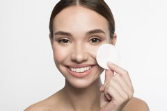 De positieve jonge vrouw gebruikt make-upvlekkenmiddel afveegt royalty-vrije stock foto